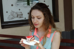 La fille mange un gâteau dans un café extérieur Photos stock