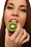 La fille mange un kiwi Images stock