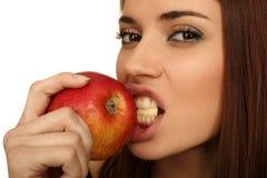 La fille mange une pomme Photographie stock