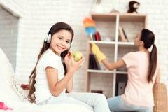 La fille mange une pomme et des repos tandis que sa mère enlève la maison photo libre de droits