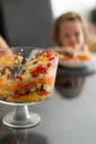La fille mangeant d'une salade posée a servi la cuvette en verre de bagatelle Photo libre de droits