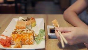 La fille mangeant les sushi et l'immersion en sauce dans le bar à sushis, se ferment  Images libres de droits