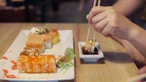 La fille mangeant les sushi et l'immersion en sauce dans le bar à sushis, se ferment  Image libre de droits