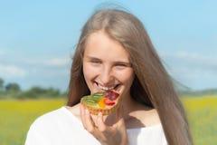 La fille mangent le gâteau sur l'air ouvert Photographie stock
