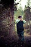 La fille manque l'arbre dans un gilet dans les bois Photo libre de droits