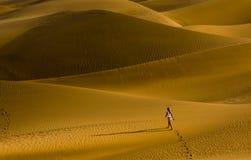 La fille marchant sur les dunes de sable Images stock