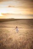 La fille marche dans le domaine avec du seigle au coucher du soleil, mode de vie Images libres de droits