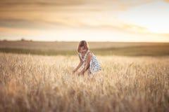 La fille marche dans le domaine avec du seigle au coucher du soleil, mode de vie Photographie stock