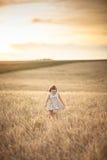 La fille marche dans le domaine avec du seigle au coucher du soleil, mode de vie Photo libre de droits