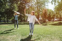 La fille marche en avant et tire le fil du cerf-volant Elle regarde au dos Sa maman tient le cerf-volant dans le ciel Image libre de droits