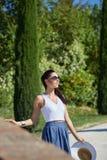 La fille marche le long de la route parmi les champs Image stock