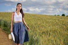 La fille marche le long de la route parmi les champs Photo libre de droits
