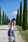 La fille marche le long de la route parmi les champs Images stock