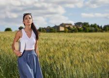 La fille marche le long de la route parmi les champs Photos stock