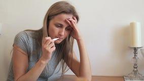 La fille mesure la température corporelle et souffre de la migraine clips vidéos