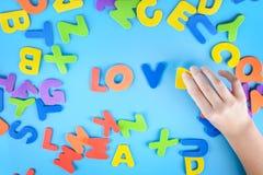 La fille met l'amour de mot hors des lettres colorées Beau fond Photo stock