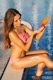La fille met la lotion de SPF de protection solaire sur son corps image libre de droits
