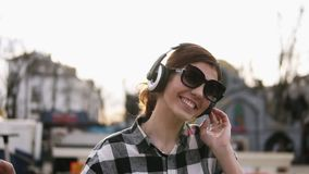 La fille met sur les écouteurs et commence à se déplacer avec les rythmes de la musique Dans des lunettes de soleil Appréciez-le  banque de vidéos