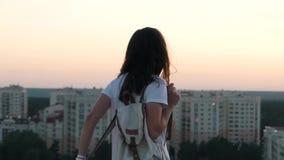 La fille met un sac à dos sur le dessus du bâtiment banque de vidéos
