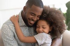 La fille mignonne aimante d'enfant d'étreinte africaine de père avec des yeux s'est fermée photos libres de droits