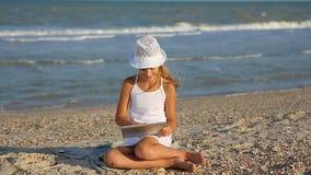 La fille mignonne 10-11 années sur la plage jouent avec le comprimé clips vidéos