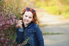 La fille mignonne apprécie l'odeur de la fleur de floraison d'amande Sain, Photo stock
