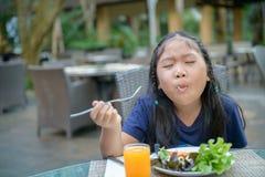 La fille mignonne asiatique appr?cient pour manger de la salade vegatable image stock