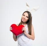 La fille mignonne avec des oreilles de lapin tenant le coeur forment Images stock