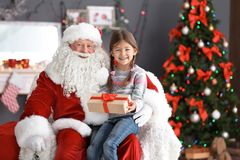 La fille mignonne avec le boîte-cadeau se reposant sur le ` authentique de Santa Claus enroulent à l'intérieur photos stock