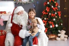 La fille mignonne avec le lapin de jouet se reposant sur le ` authentique de Santa Claus enroulent à l'intérieur photo stock