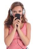 La fille mignonne d'adolescent écoute la musique sur des écouteurs photo stock