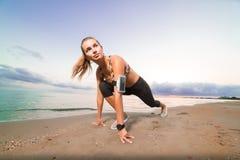 La fille mignonne d'ajustement commence à courir sur la plage au lever de soleil photos libres de droits
