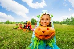 La fille mignonne dans le costume de monstre tient le potiron Photographie stock libre de droits