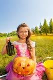 La fille mignonne dans le costume de princesse s'assied avec le potiron Image stock