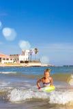 La fille mignonne dans le maillot de bain se baigne sur des vagues en mer Sunny Mediterranea Photo stock