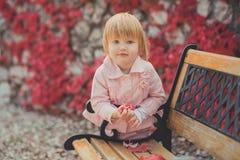 La fille mignonne de bébé avec les cheveux blonds et la joue rose de pomme appréciant l'automne de ressort chronomètrent des vaca Photographie stock libre de droits