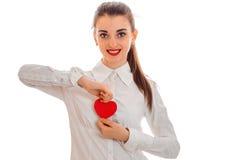 La fille mignonne de brune dans la robe noire avec gentil composent pour célébrer le jour de valentines avec le coeur rouge dans  Image stock