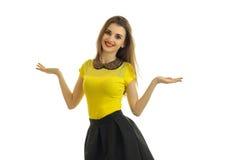 La fille mignonne de goupille- dans des vêtements lumineux tient des sourires droits et tient la paume de votre main des côtés Image libre de droits