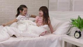 La fille mignonne de petit enfant se r?veille du sommeil dans le lit clips vidéos