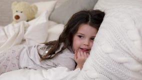 La fille mignonne de petit enfant se r?veille du sommeil dans le lit banque de vidéos