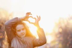 La fille mignonne de petite fille a plié ses mains une forme de coeur photos libres de droits