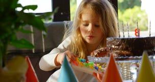 La fille mignonne disposent à décorer le gâteau d'anniversaire à la maison 4k banque de vidéos