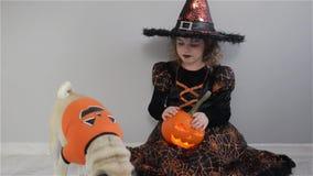 La fille mignonne et son petit chien sont habillés dans les costumes pour Halloween L'enfant dans une image de sorcier s'assied s banque de vidéos