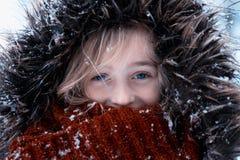 La fille mignonne a habillé l'extérieur chaud dans la neige photo libre de droits