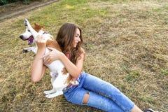 La fille mignonne joue avec son chien en parc Images stock