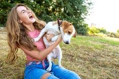 La fille mignonne joue avec son chien en parc Image libre de droits