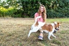 La fille mignonne joue avec son chien en parc Image stock