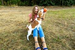 La fille mignonne joue avec son chien en parc Photo stock