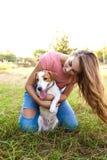 La fille mignonne joue avec son chien en parc Photographie stock libre de droits