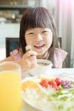 La fille mignonne mangent le petit déjeuner image stock